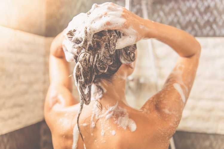 Lavare i capelli sotto la doccia (Getty Images)